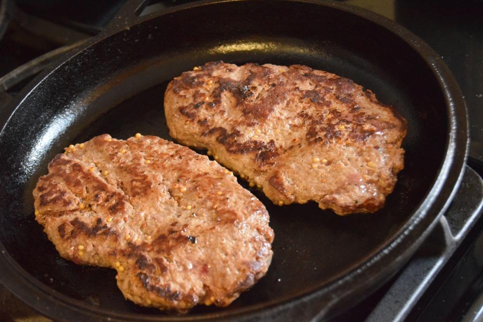 Long burger patties (mid-cooking).